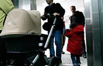 People with a pushchair entering a lift